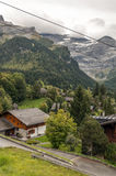 Village in the swiss Alps. In a valley witn wood house, in the background are mountains with snow on a cloudy day, it´s a vertical picture Royalty Free Stock Photos