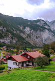 Village in the swiss Alps. In a valley witn wood house, in the background are mountains with snow on a cloudy day, it´s a vertical picture Stock Images