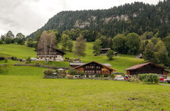 Village in the swiss Alps. In a valley Wood house, in the background are mountains on a cloudy day Stock Photos