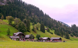 Village in the swiss Alps. In a valley Wood house, in the background are mountains on a cloudy day Royalty Free Stock Photo