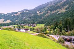Village in the swiss Alps. In a valley Wood house, in the background are mountains on a cloudy day Stock Images