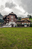 Village in the swiss Alps. In a valley Wood house, in the background are mountains on a cloudy day, it´s a vertical picture Royalty Free Stock Photos