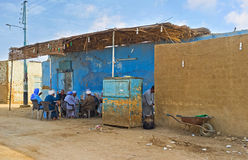 The village teahouse. NAJ' AT TUNAB, EGYPT - OCTOBER 6, 2014: The company of elderly men sits in the shady terrace of the village teahouse, on October 6 in Naj' Stock Photo