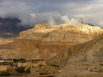The village of Tetang, Mustang. Resting at the foot of majestic mountains, the village of Tetang in Mustang, Nepal, is the last inhabited place before crossing Stock Photo