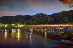 Togetsukyo Bridge at dusk, Arashiyama, Kyoto. Village and Togetsukyo Bridge above Katsura River at dusk with twilight sky in autumn, Arashiyama, Kyoto, Japan Stock Image