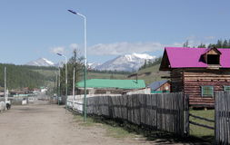 The village of Turt and mount Munch-Sardyk on the shores of lake Hovsgol. Street in the village with buildings on the mountains Munku-Sardyk in the summer Stock Photos