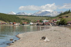 The village of Turt and mount Munch-Sardyk on the shores of lake Hovsgol. Street in the village with buildings on the mountains Munku-Sardyk in the summer Stock Photo