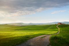 Village in tuscany; Italy countryside landscape with Tuscany rolling hills ; sunset over the farm land and country road royalty free stock photo