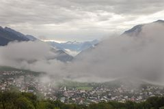 Village in typical swiss landscape of wallis or valais near sierre with clouds and mountains. Village in typical swiss landscape of wallis or valais near sierre stock images