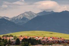 Village typique, pré d'herbe verte et montagnes à l'arrière-plan, Liptovska Mara, Slovaquie photos stock