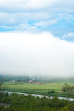The village under the cloud. Giant cloud. Mountain village. Foggy weather. Royalty Free Stock Image