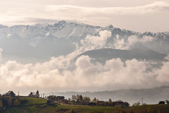 Village under the mountain clouds fog Stock Image