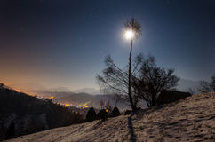 Village under the mountain at night with moon. Village under the mountain at night, with the moon nesting in a tree stock image