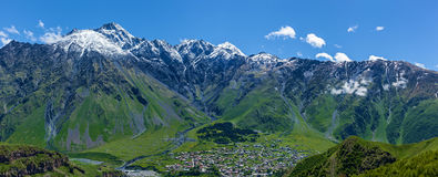 Village under the mountains of Kazbegi, Stepancminda,Sight of Ge. Village on snow-capped peaks of mountains Background In Kazbegi District,  Military-Georgian Royalty Free Stock Image