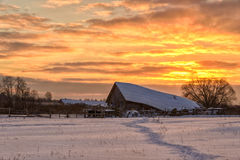Village under snow at dawn. Landscape of a barn in a snowy field with a split rail fence Stock Photos
