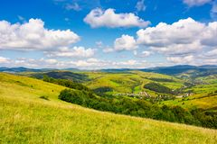 Village in the valley of Carpathian mountains. Lovely countryside scenery in early autumn with clouds on a blue sky over the distant ridge stock photos