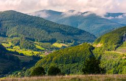 Village in the valley of Carpathian mountains. Lovely countryside scenery in early autumn with clouds rising from the forest on the distant ridge Stock Images