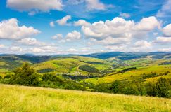 Village in the valley of Carpathian mountains. Lovely countryside scenery in early autumn with clouds on a blue sky over the distant ridge stock photo