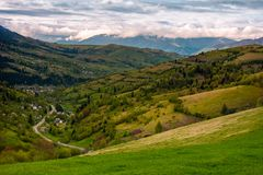 Village in the valley on a cloudy day. Lovely springtime landscape in mountains Stock Photos
