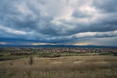 Dramatic cloudscape near Bulgarian village. Village in valley on cloudy rainy day. Panoramic landscape of village with multi colored roofs Royalty Free Stock Image