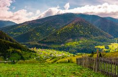 Village in valley on a cloudy springtime day. Fence on hillside above beautiful rural area Stock Photos