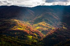 Village in a valley down the hill among forest. Beautiful autumn scenery in mountains Royalty Free Stock Photography