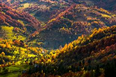 Village in a valley down the hill among forest. Beautiful autumn scenery in mountains Stock Images