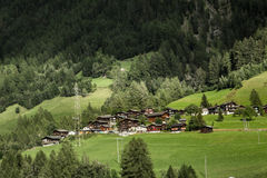 Village in the valley of swiss Alps. Tiny village in the valley in Swiss Alps. Group of little houses royalty free stock photography