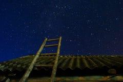 village Vieille échelle en bois se penchant contre la grange avec un toit d'ardoise dans le ciel d'étoile de nuit L'escalier mène Photographie stock