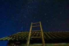village Vieille échelle en bois se penchant contre la grange avec un toit d'ardoise dans le ciel d'étoile de nuit L'escalier mène photographie stock libre de droits