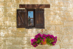 Cyprus window. Old wooden village window in the stone wall with colorful flowers underneath in Fasoula village, Cyprus Royalty Free Stock Photo
