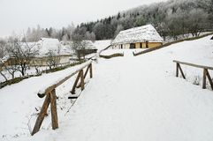A village in winter. Authentic Eastern Europe village in winter with thatched roof huts Stock Photos
