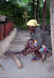 Village woman chopping  wood Royalty Free Stock Photography