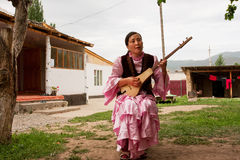 Village woman play on traditional Kyrgyz musical instrument Komuz Royalty Free Stock Image