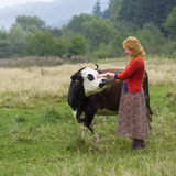 Village woman standing near a cow in the meadow Stock Photo