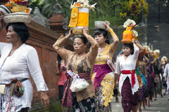 Village women carry offerings of food baskets Stock Image