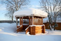 Village. Wooden arbor decorated with national Russian woodcarving. Winter. Clear day. Snow. Village. Wooden arbor decorated with national Russian woodcarving Stock Photo