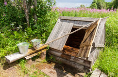 Village wooden water well with the open door and a metal buckets Stock Photos