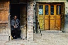 villageois local s'asseyant à sa porte à la maison observant la foule pour passer par images stock