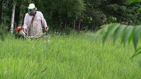 Villager cut grass with handheld power trimmer, focus change. Villager with mask cut tall grass with handheld power cutting machine trimmer, focus change stock video