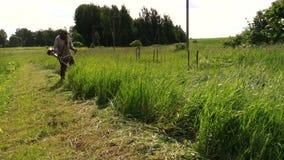 Villager cut grass with manually petrol trimmer, garden work. Villager cut tall grass quietly slowly with manually operated petrol trimmer, season summer garden stock footage