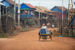 Villager on dirt road of Tonle Sap, Cambodia. Villager riding motor scooter with cart down dirt streets of Tonle Sap village in Cambodia on sunny day Royalty Free Stock Photos