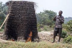 Villager making bricks in kiln, Uganda, Africa. Ishasha, Uganda - February 26, 2017 :  Villager using handmade kiln used to fire harden mud bricks in rural Royalty Free Stock Images