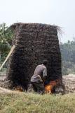 Villager making mud bricks, Uganda, Africa. Ishasha, Uganda - February 26, 2017 :  Villager using handmade kiln used to fire harden mud bricks in rural Uganda Stock Photos
