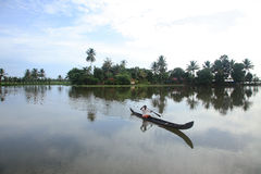 A villager rows a traditional boat in the backwaters Royalty Free Stock Images