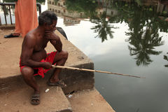 A villager uses a fishing rod to fish in  backwaters Stock Image