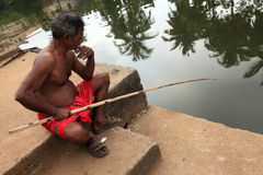 A villager uses a fishing rod to fish in  backwaters Stock Photo