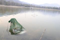 Villagers are catching fish by fish trap net trap. In reservoir stock images
