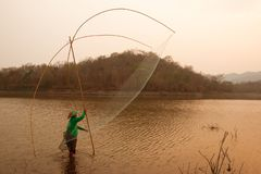 Villagers are catching fish by fish trap net trap. In reservoir stock image