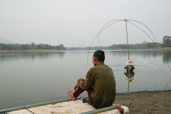 Villagers are catching fish by fish trap net trap. In reservoir stock photography